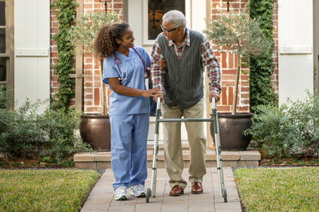 Nurse helping patient with walker outside home
