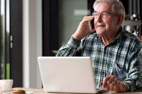 Senior man on the phone with provider and using laptop
